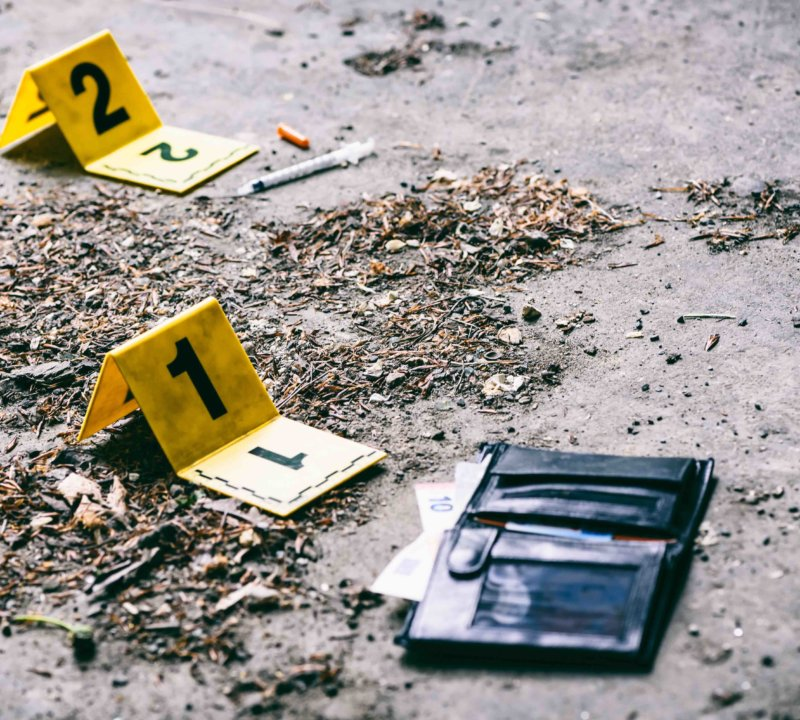 Crime investigation, yellow crime scene marker next to the wallet on the ground
