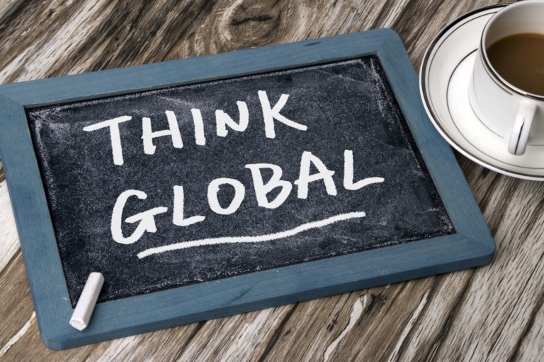 """The words """"Think Global"""" written on a chalkboard with a coffee cup nearby"""