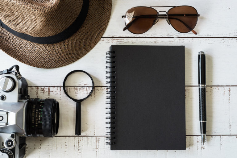 Black notebook, pen, magnifying glass, hat, sunglasses, and retro camera on wooden background